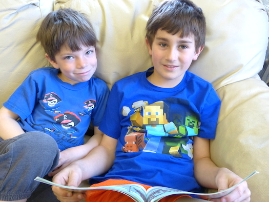 older boy reading to younger boy
